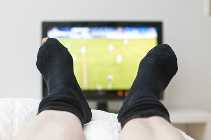 Laying in bed and watching a game on tv in dark socks with a hole
