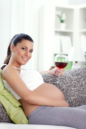 pregnant woman drinking glass of  wine at home