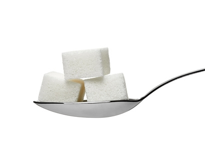 close up of  sugar cubes in a spoon on white background with clipping path