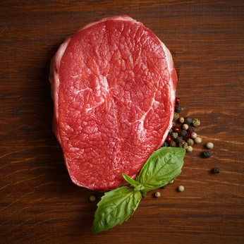 fresh raw steak with pepper and basil on the wooden board.