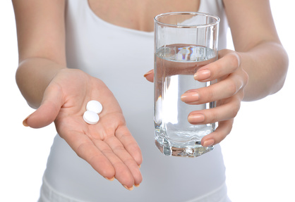 hand with pills medicine tablets and glass of water for headache on a white background