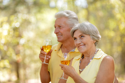 Mature couple drinking wine over natural background