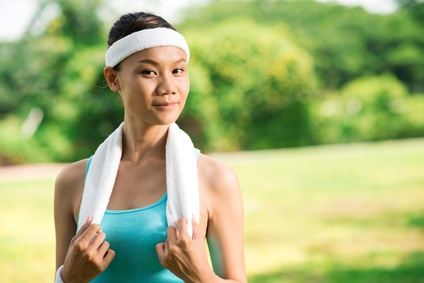 Copy-spaced image of a cheerful sportswoman in sweatband in the park