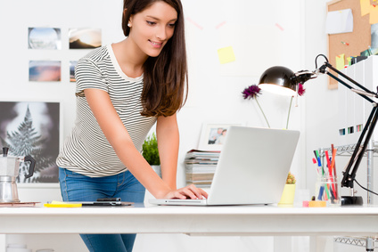 Portrait of young woman working with laptop in her workspace